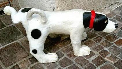 壁にマーキング行為を行っている犬の置物